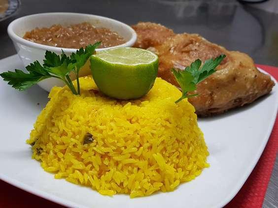 Riz parfumé jaune, accompagné avec une sauce aux oignons et du poulet fri