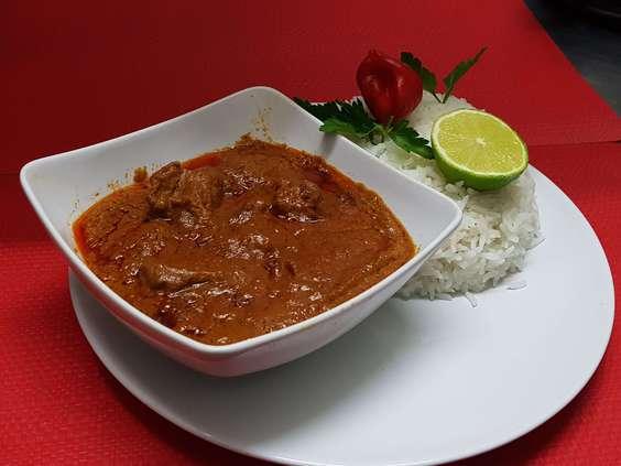 Du riz blanc parfumé accompagné d'une sauce à la pâte d'arachide avec de la viande de boeuf.